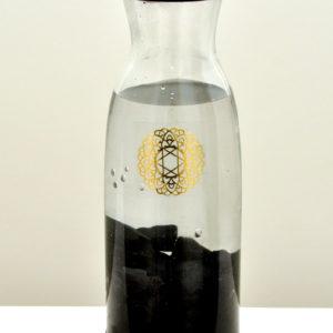 Shungite in glazen fles- Shungite water filter, Shungite ook wel genaamd The Miracle Stone wordt alleen in de buurt van de kleine nederzetting genaamd Shunga in Karelië, Rusland gevonden. Shungite zuivert water en lucht, beschermt mensen tegen elektromagnetische straling van verschillende aard. Shungite versterkt het immuunsysteem en bezit geneeskrachtige eigenschappen. Naast de geweldig reinigende en helende eigenschappen bezit het ook spirituele eigenschappen en het kalmeert en troost. Het absorbeert letterlijk negatieve energie en zorgt voor meer innerlijke rust. Met de Shungite kun je water revitaliseren. Je ontvangt een pakketje van 300 gram. (de stenen goed wassen voordat je deze toevoegt aan de kan)